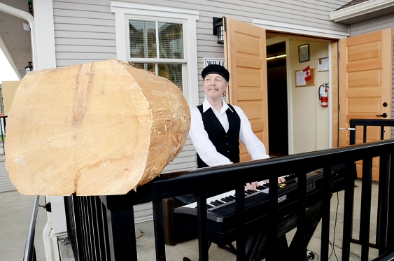 Willie MacCalder performed at the Grand Re-Opening of the restored Willoughby Hall. A piece of the original cedar logs which formed the Hall's foundation since 1937 was on display. Photo by Langley Advance